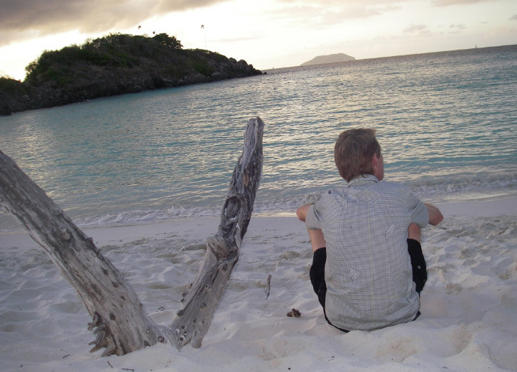 man sitting near driftwood in sand at Trunk Bay sunset