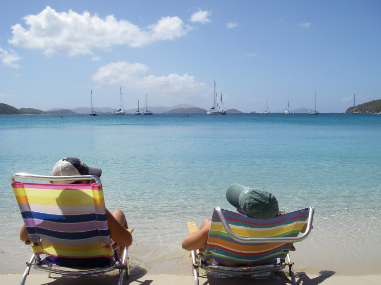 Couple in beach chairs enjoying sailboats in the blue water on St John Beach